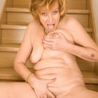 Mature redhead doffs a dress and pretties to pose totally naked on wooden stairs
