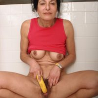 Mature woman strips naked in the kitchen before taking a banana to her hairy pussy