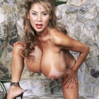 Older Asian woman Minka shows her massive tits before exposing her trimmed twat