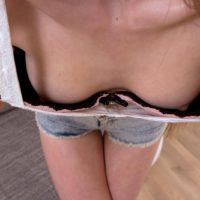 Petite teen Malvina uncups her small tits on a couch while wearing cutoff shorts