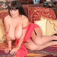 Thick solo model Arianna Sinn lets her massive tits loose from a dress in tan nylons