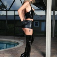 Blonde chick Alina Long shows her small tits in a latex miniskirt and thigh high boots