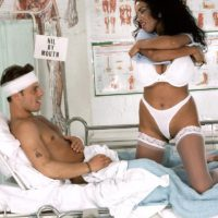Busty ebony nurse Angelique seduces a male patient during upskirt action on a bed