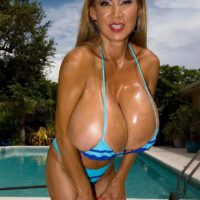 Chesty Asian lady Minka models a pair bikinis outdoors in close proximity to a pool