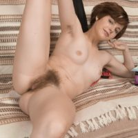 Leggy redhead amateur Aria wears her hair short while showing her natural pussy