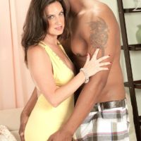 Old woman Gillian Sloan showcases her shaved pussy on the lap of young black man