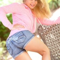 Cute blonde teen Mindy exposes her firm boobs and thong clad ass on a patio