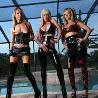 Blonde dommes Alexia, Tyler and Alina model latex wear in front of a swimming pool