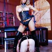 Hot blonde domme Alexis Fawx mouth fucks a sissy with a strapon cock in a dungeon