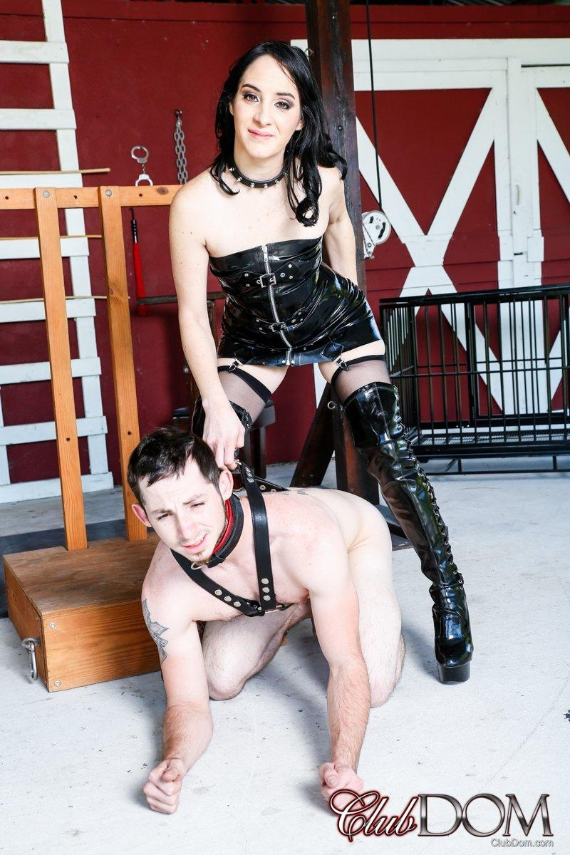 Brunette chick Sarah Dice dominates a male submissive in latex attire and long boots