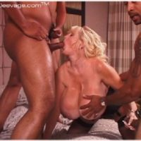 Big titted older blonde Kayla Kleevage takes part in an interracial gangbang on her bed