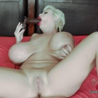 Big titted platinum blonde Claudia Marie sucks on a dildo while masturbating on a bed