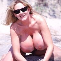 Blonde solo model Kayla Kleevage frees her fake tits from a bikini while at the beach