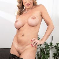 Busty mature maid Kenzi Foxx licks a nipple while getting naked for dildo sucking