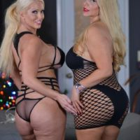 Curvy older blonde Karen Fisher and her lesbian girlfriend break out a sex toy on a bed