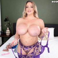 Hot MILF Holly Wood sets her enhanced boobs free of a bra after twerking her booty