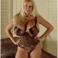 Mature blonde woman Kayla Kleevage sets her enhanced breasts and bush loose on a sofa