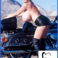 Mature model Kayla Kleevage puts her giant tits on display in leather by a motorcycle