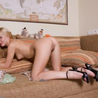 Blonde amateur finger spreads her natural pussy on a chesterfield in ankle strap heels