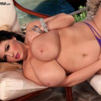 Big titted brunette Arianna Sinn plays with her nipples after getting naked on a patio