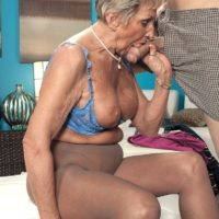 Blonde granny Sandra Ann sucks her younger lover's cock on a bed in pantyhose