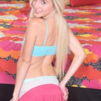 Blond teenager Naomi Forest removes her micro-skirt and pulls down white hosiery