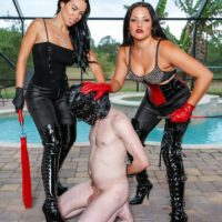 Black-haired Domme Kylie Rogue and a girlfriend abuse her hooded subby husband beside pool