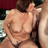 Busty cougar Yasmine Beale gets on her knees to give a younger man a blowjob