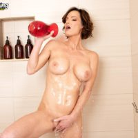 Busty middle-aged lady Ainsley Adams gets cleaned up in a bathtub after waking up from a snooze