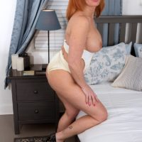 Busty middle-aged redhead Nina Lakes sucks on a dildo during amateur solo action in a bedroom