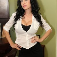 Glasses attired black-haired chick Emmanuelle London flashes her smooth-shaven pussy in tights