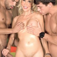Long legged blonde granny Erica Lauren is stripped naked before sucking two big cocks