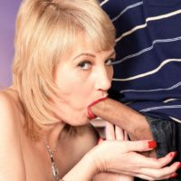 Mature blonde woman Dixie Reynolds sports red lips while sucking her lover's cock during foreplay