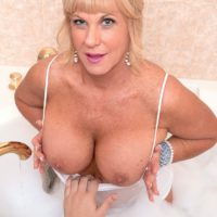 Mature blonde woman Zena Rey jerks on a large cock while taking a bubble bath