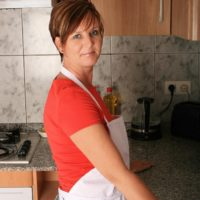 Senior housewife with short crimson hair lets out her massive naturals for her first nude poses