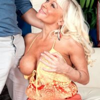 Mature platinum blonde Farrah Rose bares her boobs before licking and jerking a cock