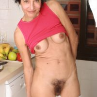 Elderly dame strips nude in the kitchen before taking a banana to her hairy gash