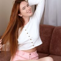 Natural redhead Gina plays with her long hair while stripping off her clothes