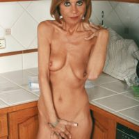 Thin mature doll revealing flappy tits and bare booty in kitchen for a nude spread