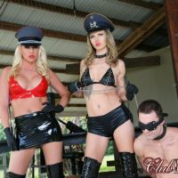 2 mistresses in hats and long boots lead a male submissive by a leash