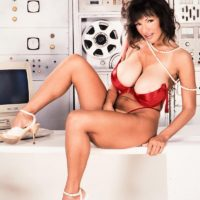 Dark haired businesswoman BriAnna demonstrates her amazing gams and huge titties at once
