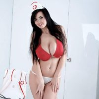 Dark haired nurse Sha Rizel removes her uniform to pose in her boulder-holder and panties