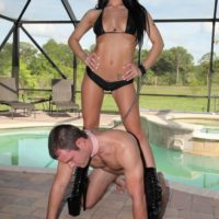 Wonderful dark-haired female Adriana Lynn makes a collared male submit to her wishes in stiletto boots
