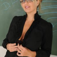 Mature sandy-haired dame attired in glasses strips naked in front of a chalkboard in a classroom