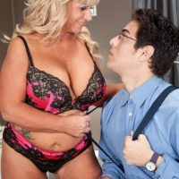 Round over fifty MILF Zena Rey releasing giant boobs from a brassiere while seducing a dude