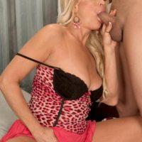 Tempting yellow-haired grandma Natasha fellates a big black dick in a micro-skirt