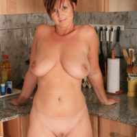 At housewife with short crimson hair looses her humungous natural tits for her first naked poses