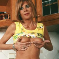 Middle aged housewife removes denim jeans and skivvies to model naked in her kitchen