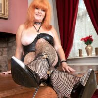 Busty mature redhead Melanie Taylor sports nipple clamps while paddling her big butt