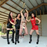 Brutish females with dark hair torture a male submissive while dressed in latex and long boots
